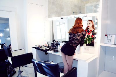 woman at vanity, model holding roses, shiny red hair, woman looking into mirror