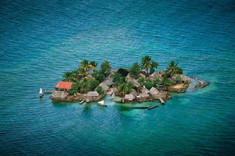 vista aérea de uma ilha com casas de palha, ancoradouro e canoas