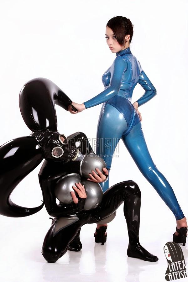 deux femmes en tenues latex une gonflée avec des cornes et god noir et grise et une dans une tenue bleue
