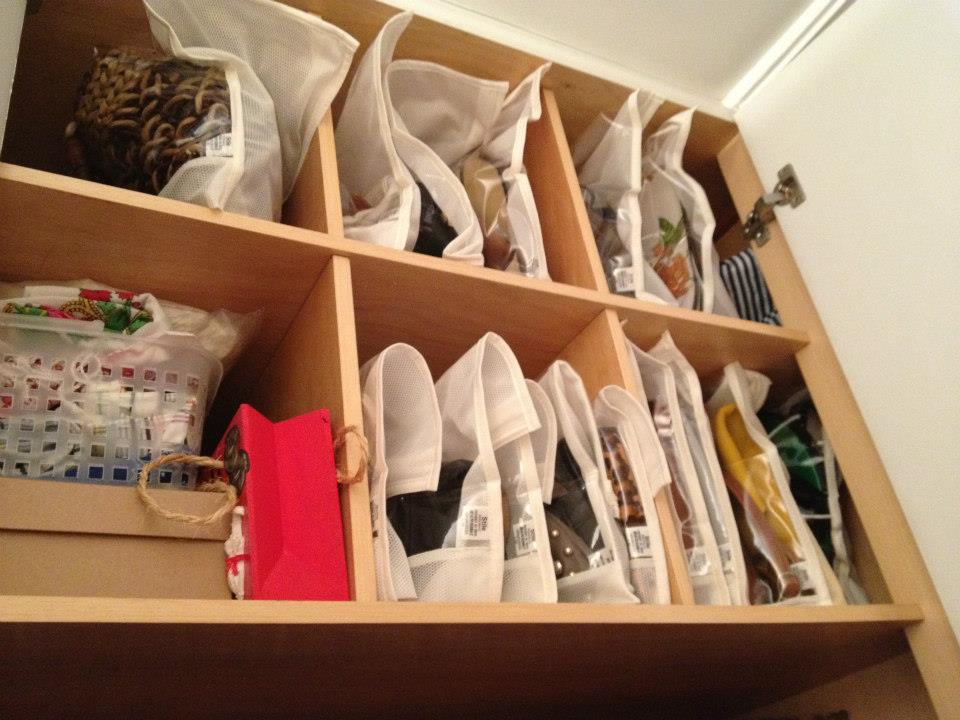 Organização de bolsas em nichos acondicionadas em saquinhos de TNT