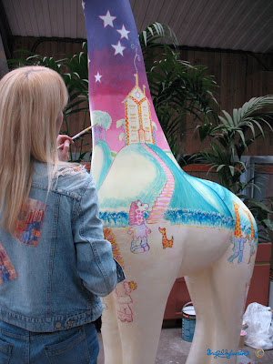 Giraffe artist Ingrid Sylvestre painting Stand Tall for Giraffes sculpture