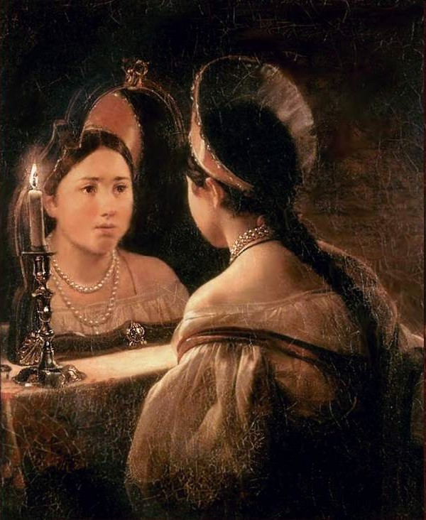 A young Russian girl gazes into a mirror next to a candle