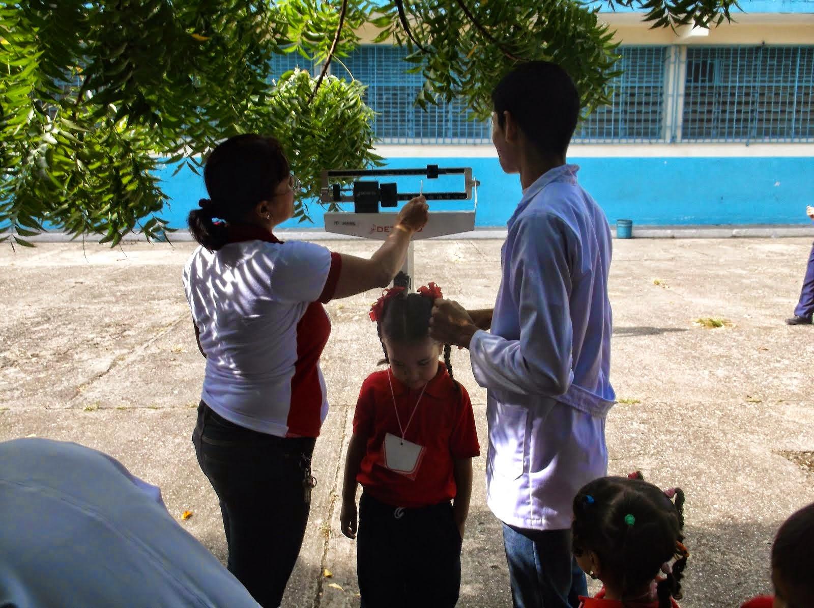 Personal de Barrio Adentro tallando y pesando a las niñas (os)