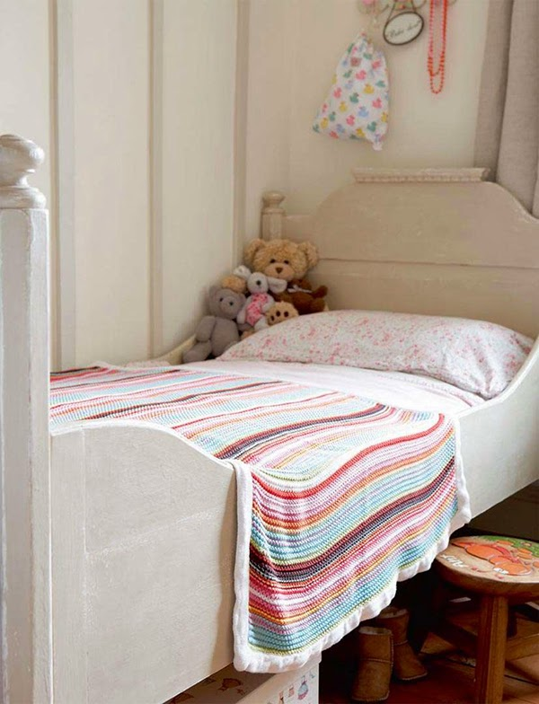 Colourful knitted blanket in cottage chic children's room
