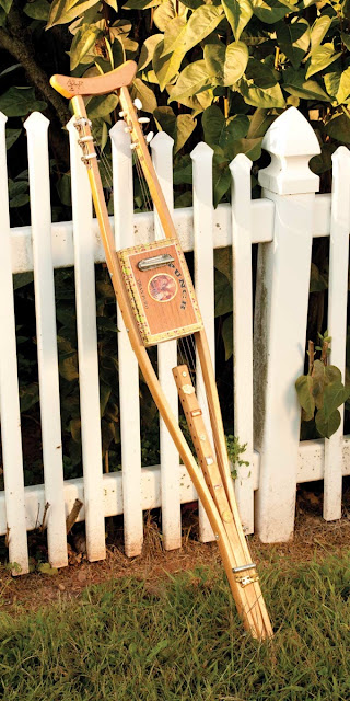 crutch cigar box guitar leaning on a fence