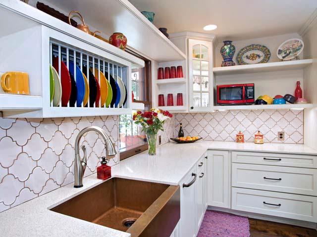 the plate rack above the sink displays a collection of colorful plates while storing them safely it adds an element of interest and uniqueness says - Kitchen Design Austin