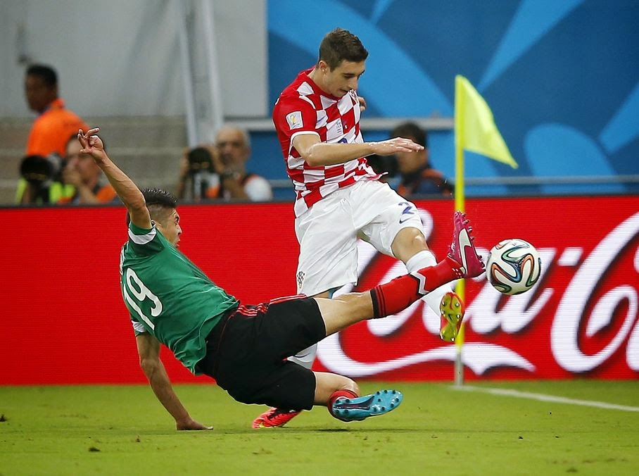 Mexico's Oribe Peralta, left, fights for the ball with Croatia's Sime Vrsaljko during the group A World Cup soccer match between Croatia and Mexico at the Arena Pernambuco in Recife, Brazil, Monday, June 23, 2014.