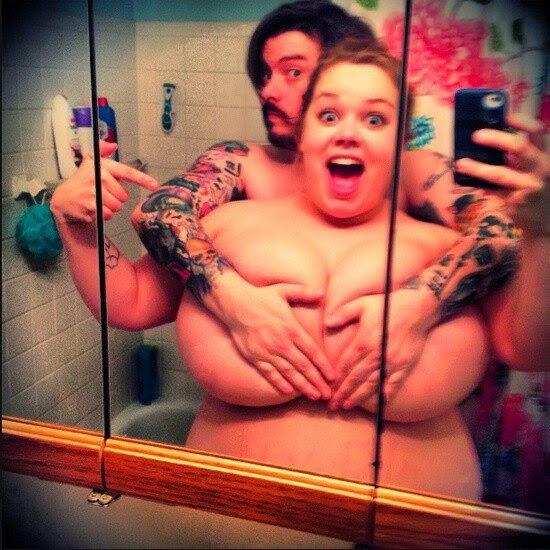photo sexy et pétillante d'un autoportrait d'un couple avec une femme fonde et son homme tatoué cachant ses gros seins de ses mains