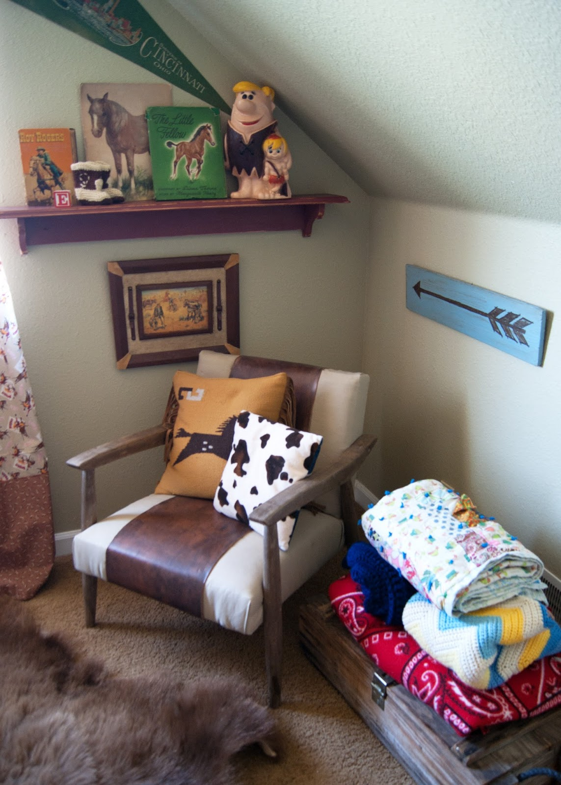 Cozy reading corner in Western Bedroom - mid century chair, blankets and arrow sign