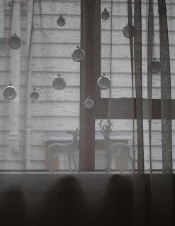Two ceramic deer sit on the windowsill.