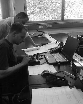 In einem Berufsbildungzentrum arbeiten zwei jungen Männer mit Schaltkreis, Computer und Bleistift.