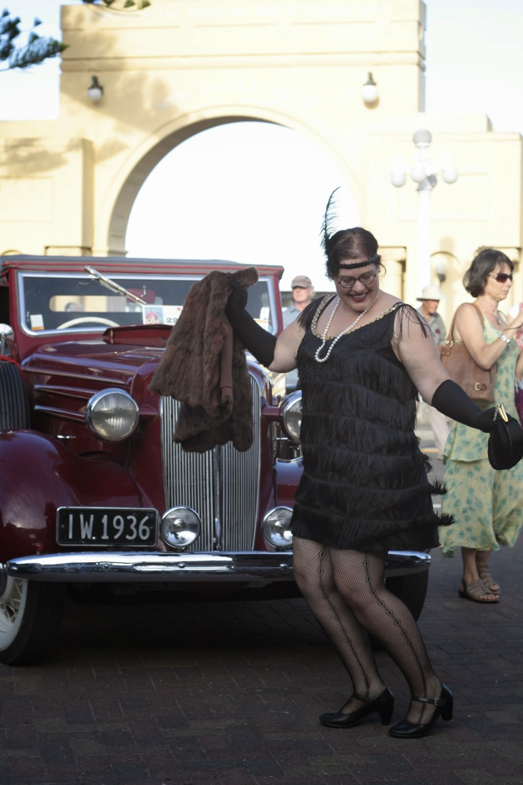 Me in a black flapper's costume, with fringing and a headband. I have fishnets and carry a fur.