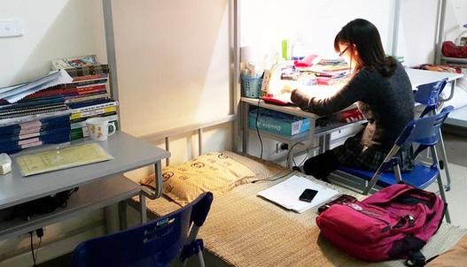 Gian phòng trong khu chung cư giá rẻ chỉ có duy nhất một nữ sinh đang học bài còn lại, tất cả đều đang say ngủ giữa buổi chiều