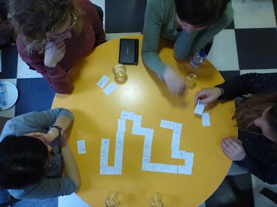 Vogelperspektive: Gelber Tisch und junge Leute, die Domino spielen, die Zweite