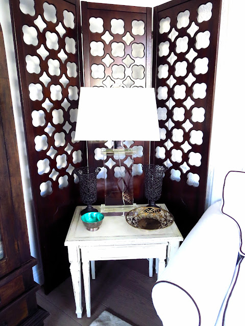 Vintage wood screen and a white side table with a crystal lamp and vintage bowls in Coco of COCOCOZY's living room