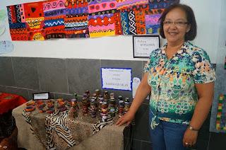 A diretora Ana Maria de Oliveira Mendonça ao lado de alguns trabalhos em exposição