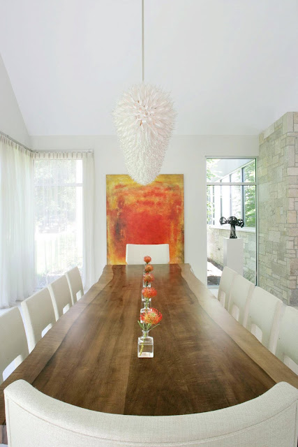 dining room in a modern farmhouse with white chandelier, long wood table, white chairs, large windows and a red and yellow piece of modern art on the wall