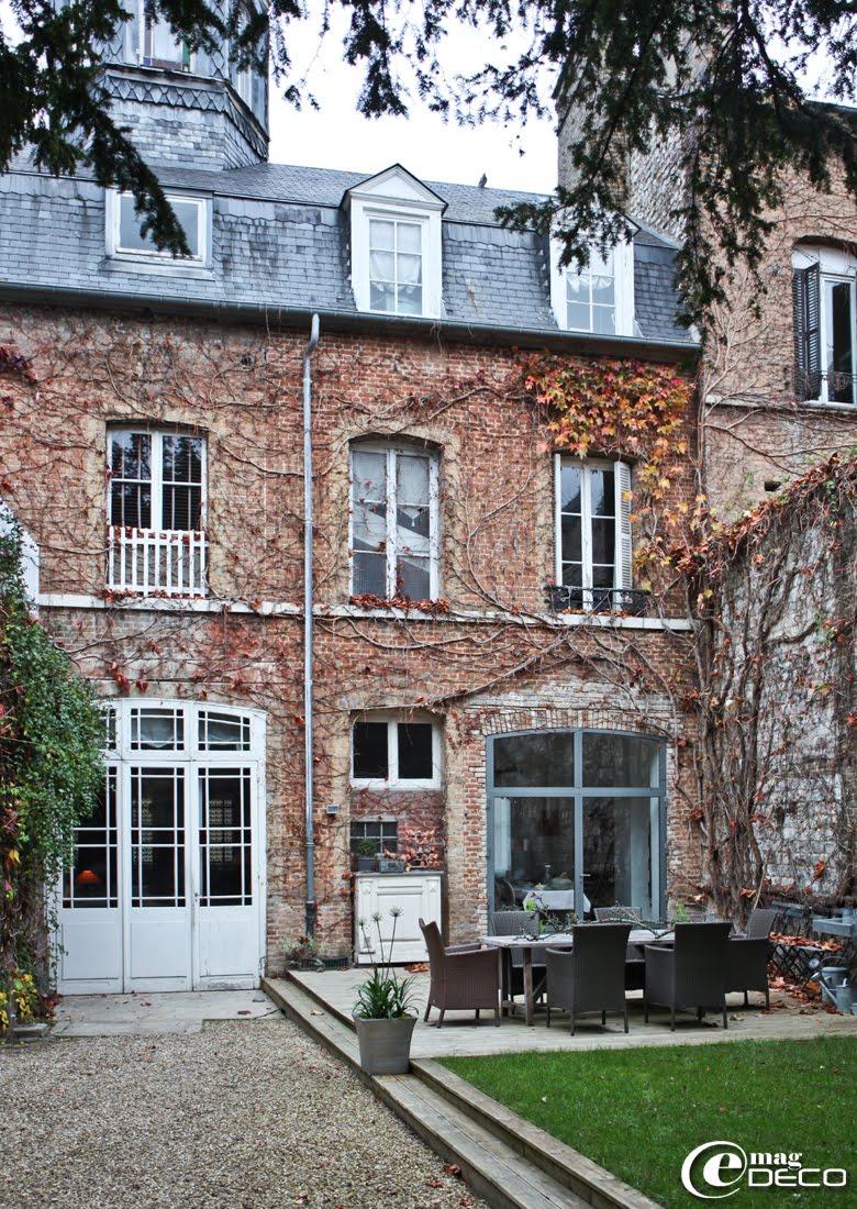 La maison de Chantal du blog 'L'Univers d'Anaïs', vue sous la frondaison des grands ifs, façade en brique et zinc couronnée d'un belvédère sur plan hexagonal