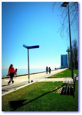 Imagem do calçadão às margens do Rio Tejo, Parque das Nações, Lisboa, com a Torre Vasco da Gama ao fundo.