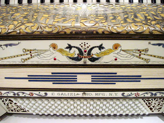 The E. Galizi Bro. White-and-Gold Pearled Piano Accordion is under lock and key at the Old New York Accordian Museum