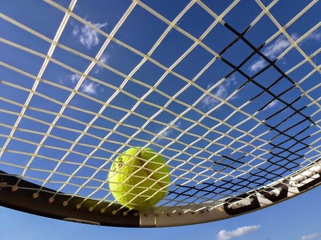 テニスラケットにのるテニスボールの画像