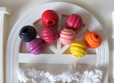 Eight coloured wooden beads, arranged in the fanlight of a dolls' house miniature fanlight.