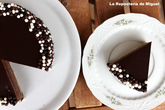 Vista desde arriba porción cortada sobre plato de porcelana blanco con flores a la derecha, y a la izquierda pastel sobre plato blanco. Todo ello sobre una mesa de madera oscura.