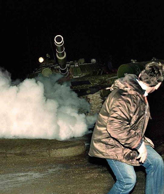 Lituano foge de tanque soviético durante a tomada da estação de rádio e TV em Vilnius, 13.01.1991