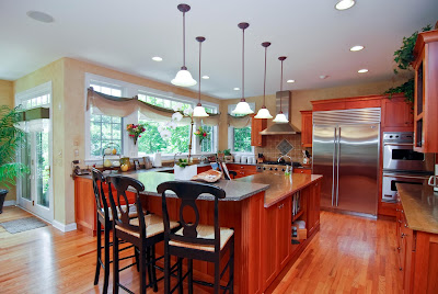 wide kitchen with reddish kitchen furniture finish and beautiful lighting fixtures