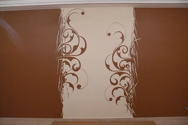 Malowanie grafiki ściennej przedstawiającej artystyczne esy floresy
