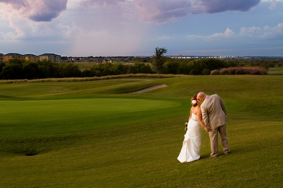 couple strolling and kissing on the golf course