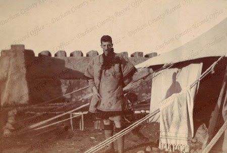 A soldier of the 1st Battalion, The Durham Light Infantry, standing outside a tent at an army camp, captioned 'Band Chief', taken in India, 1916 (D/DLI 2/1/277(15))