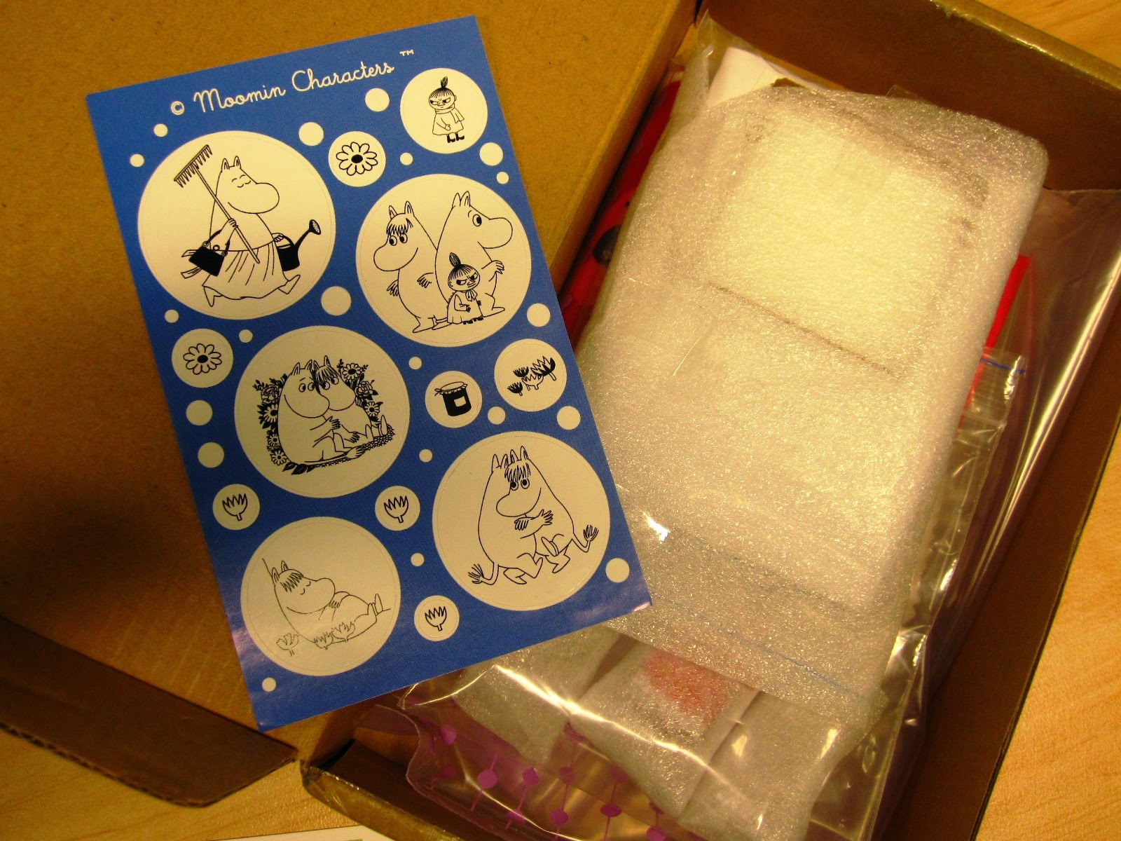 Opened package with Moomin stickers and wrapped contents.
