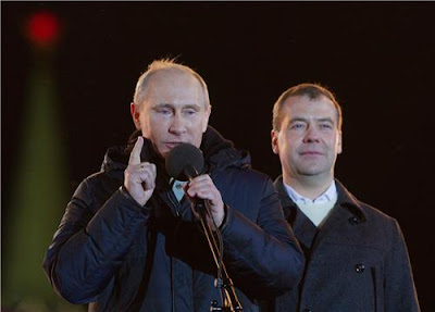 Putin speaks at a demonstration, with Medvedev