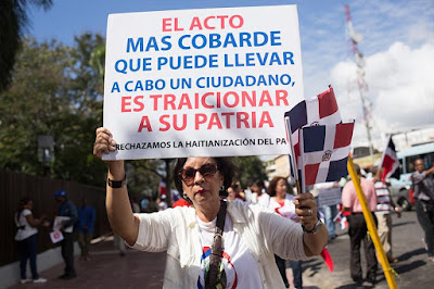 "A woman holds a sign during a protest on Dominican Independence Day in santo  Domingo protesting the ""Haitianization"" of the Dominican Republic,  February 27, 2015 (Fran Alfonso)"