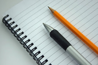 lined notepaper and pen and pencil
