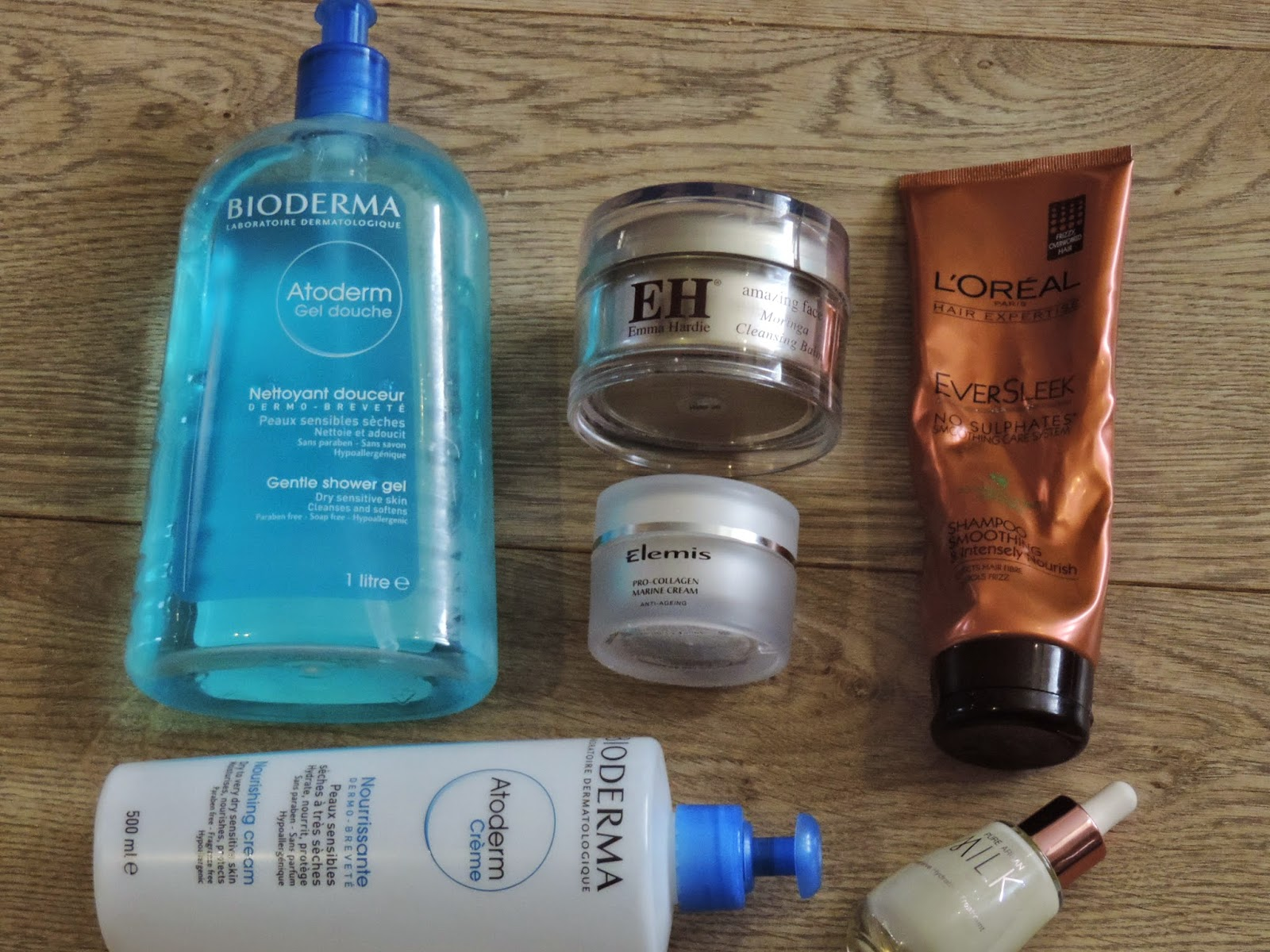 (Clockwise): Bioderma Atoderm Gentle Shower Gel, Emma Hardie Cleansing Balm, L'Oreal Ever Sleek Shampoo, Josie Maran Milk Treatment, Bioderma Atoderm Moisturiser, Elemis Pro Collagen Marine Cream.