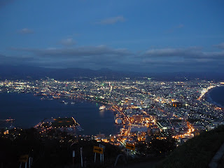 Nightview of Hakodate and it's sparkling lights and ocean from Mt Hakodate with road in the foreground