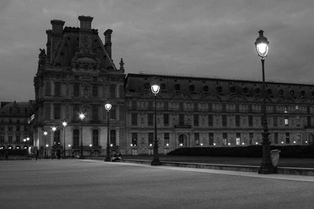 lighted street lamps outside the Louvre at night