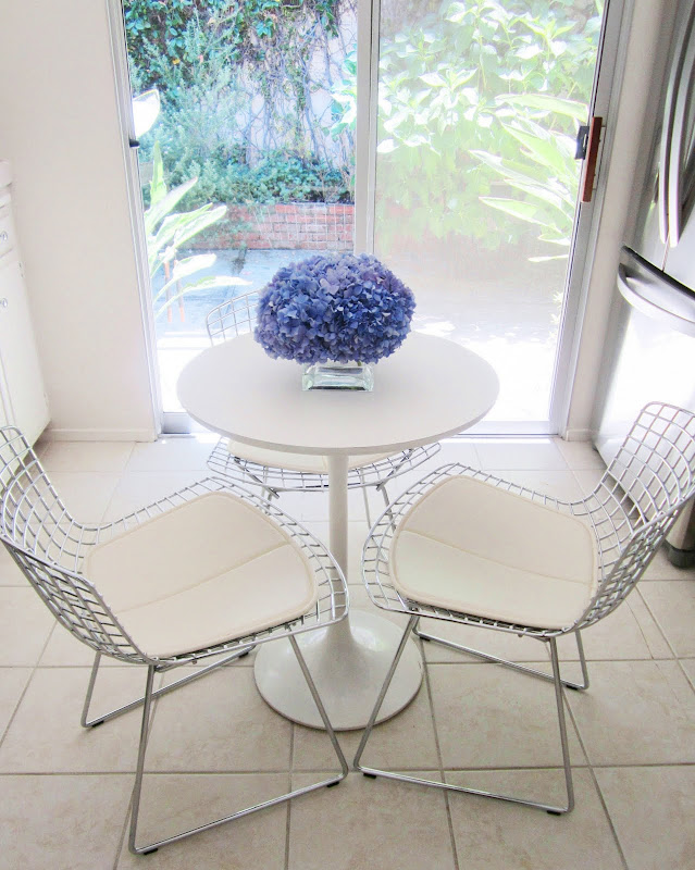 A pave arrangement of purple hydrangea on a white kitchen table surrounded by three wire chairs with white cushions