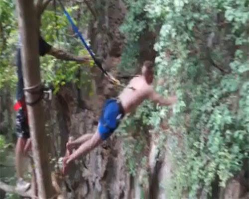 Jovem pula de árvore preso apenas por ganchos enfiados na pele