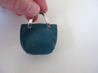 Hand holding up a dolls' house miniature leather handbag with metal straps.