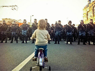 funny police photo: little boy with the bike stopped in front of the special police unit