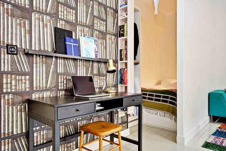 Czarne biurko, drewniany taboret, tapeta z książkami, biały regał z ksiązkami wiszący. Półka Ribba