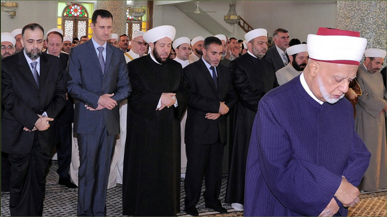 16-Syrian+President+Bashar+Al+Sad+Praying+Eid.png