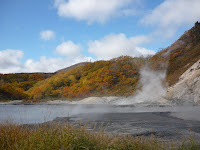 Large sulfous lake and near noboribetsu-onsen emitting steam  with hill and blue sky with a few clouds in the background