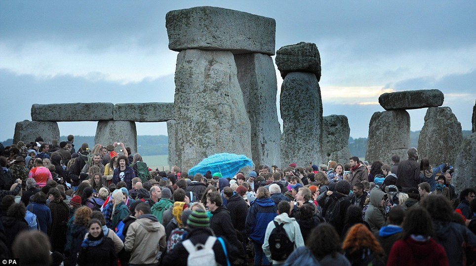 Can anyone tell us when the sun is coming up? 18,000 gather at a cloudy Stonehenge for all-night summer solstice party