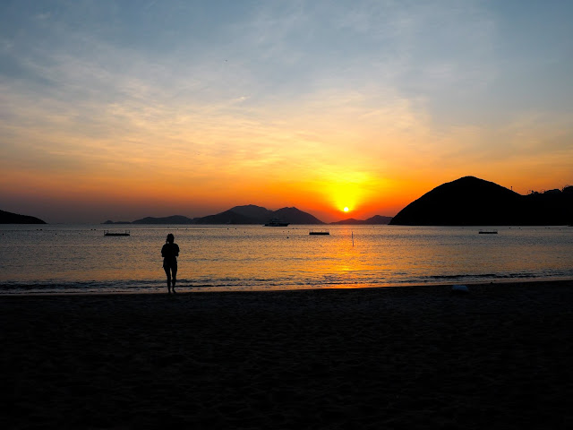 Silhouette of a girl on the beach, with the sunset over the ocean on Repulse Bay Beach, Hong Kong