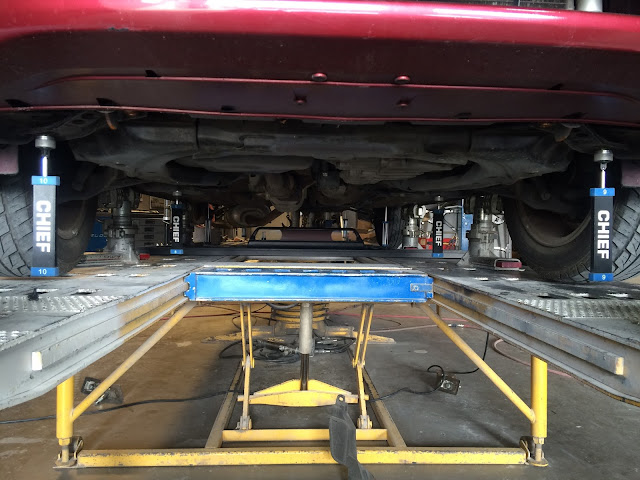 Vehicle on frame rack being re-aligned
