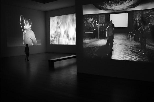 Sala com três projecções em simultâneo, Uma criança numa das telas e uma criança a passar junto a essa tela